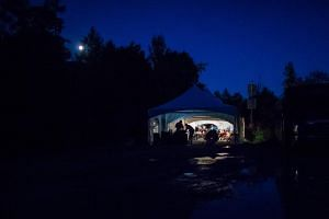 Refugees who crossed the Canada/US border illegally near Hemmingford, Quebec as they are processed in a tent after being arrested by the RCMP.