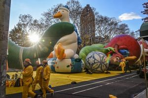 Workers on the Macy's inflation teams walk past inflated balloons near Central Park ahead of the Macy's Thanksgiving Day parade in New York City on Nov 22, 2017.