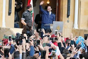 Mr Saad al-Hariri greeting his supporters outside his home in Beirut yesterday. He has said that all Lebanese must commit to keeping the country out of regional conflicts, a reference to the powerful Iran-backed Hizbollah whose regional military role