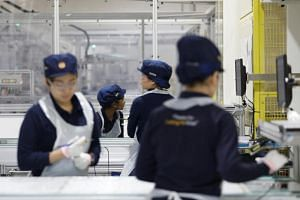 Employees work at a production line during a tour of an REC solar panel manufacturing plant in Singapore.