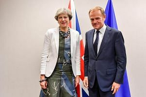 British Prime Minister Theresa May is welcomed by European Council President Donald Tusk for a bilateral meeting during an EU summit in Brussels.
