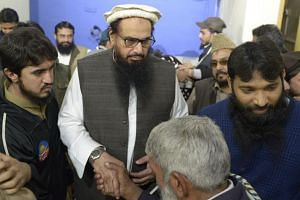 Hafiz Saeed (second from left), head of the UN-listed terrorist group Jamaat-ud-Dawa (JUD), meets with supporters after offering Friday prayers at Jamia Masjid Al-Qadsia following his release in Lahore on Nov 24, 2017.