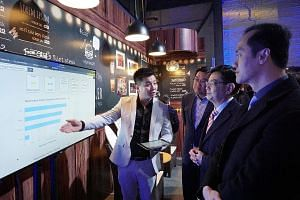 Finance Minister Heng Swee Keat being shown around the exhibits at the CapitaLand Tech and Innovation Summit at 798 Art Zone in Beijing yesterday.