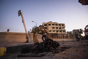 The remains of a car which exploded in front of a national security building are pictured in northern Cairo's district of Shubra on Aug 20, 2015.