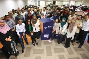 Berita Harian editors and journalists pose for a group photo in their newsroom.