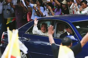 Pope Francis (centre) is welcomed by the crowd along a road in Yangon, Myanmar, on Nov 27, 2017.