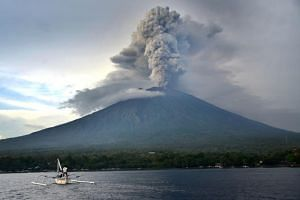A fisherman steers a traditional boat as Mount Agung erupts, seen from the Kubu sub-district in Karangasem Regency on Indonesia's resort island of Bali on Nov 28, 2017.