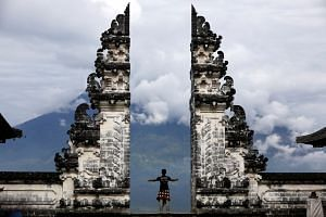A Balinese man stands at the gate of Lempuyang temple looking towards Mount Agung volcano, in Karangasem Regency, Bali, Indonesia, on Dec 2, 2017.