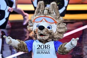 A performer dressed as Zabivaka, the official mascot for the 2018 Fifa World Cup, gestures on stage during the Final Draw for the football tournament at the State Kremlin Palace in Moscow on Dec 1, 2017.