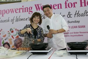 Dr Amy Khor and celebrity chef Eric Teo cooking healthy Nyonya chap chye at Hong Kah North Community Club on Sunday (Dec 3). She said that a more affluent society and a wider range of food choices were possible reasons for the increase in food waste.