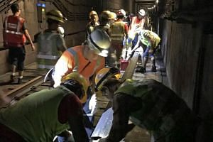 Officers from the Singapore Civil Defence Force, PUB, Land Transport Authority and SMRT worked through the night on Oct 7 to clear the water in the tunnel between Bishan and Braddell stations.