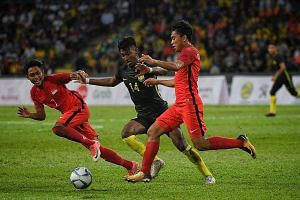 Singapore's Muhaimin Suhaimi (No. 7) and Syahrul Sazali vying for the ball with Malaysia's Syamer Kutty Abba in their SEA Games group match in August. The Young Lions lost 1-2 to their arch-rivals and did not make the semi-finals for the second strai