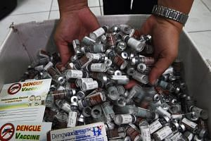 A medical worker holds up used vials of Sanofi's dengue vaccine Dengvaxia in Manila on Dec 5, 2017.