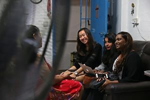 Temasek Polytechnic students (from right) Vishnupriya Raja Mohan, 17, Belinda Abraham, 18, and Megan Tan, 17, speaking to a single mother to understand her situation better. They have put the information in an advocacy report, which will be sent to a