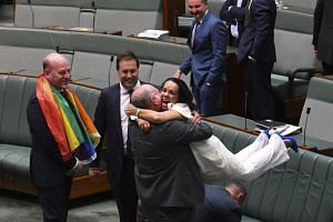 Liberal MP Warren Entsch lifting up Labor MP Linda Burney as they celebrate the passing of the Marriage Amendment Bill in the House of Representatives at Parliament House in Canberra yesterday.