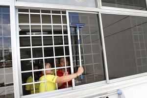 A file photo of maids being trained on how to safely clean windows.