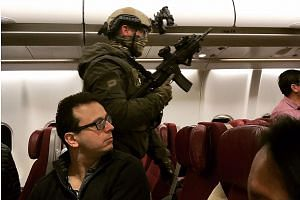 A heavily-armed policeman walking through Malaysia Airlines flight MH128 to arrest the Sri Lankan man after an emergency landing in Melbourne.