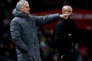 Manchester United's manager Jose Mourinho (left) and Manchester City's manager Pep Guardiola during the English premier league soccer match at Old Trafford Stadium in Manchester, Britain, on Dec 10, 2017.