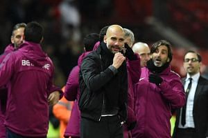 Manchester City's manager Pep Guardiola (centre) celebrates at the end of the English Premier League football match between Manchester United and Manchester City at Old Trafford in Manchester on Dec 10, 2017.