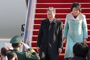 South Korean President Moon Jae In and his wife Kim Jung Sook arriving in Beijing for the start of their state visit, on Dec 13, 2017.
