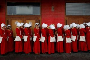 Women dressed as handmaids promoting the Hulu original series The Handmaid's Tale stand along a public street during the South by Southwest Music Film Interactive Festival 2017.