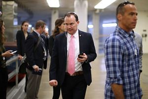Republican Senator from Utah Mike Lee (centre) is undecided on the tax Bill.