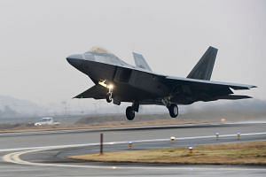 A US Air Force F-22 Raptor stealth jet taking off at a South Korean air base.