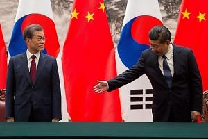 Chinese President Xi Jinping (right) with South Korean President Moon Jae In at a signing ceremony at the Great Hall of the People in Beijing on Thursday. The two leaders have pledged to improve bilateral ties and work to resolve the North Korean nuc