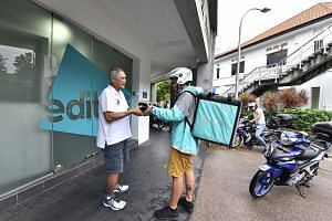 New Ubin Seafood co-founder Pang Seng Meng with a Deliveroo rider. The meats and rice bowl dishes are quick to prepare and suitable for delivery, offering access to a new market without alienating the eatery's existing customer base, said Mr Pang.