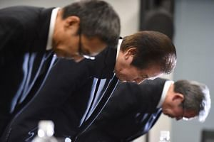 Mitsubishi Materials Corp president Akira Takeuchi (C) bows at the beginning of a press conference after the group admitted to falsifying product data in Tokyo on Nov 24, 2017.