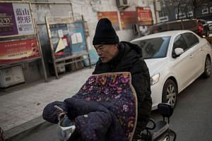A man commutes along the street on a cold day in a northern Chinese village.