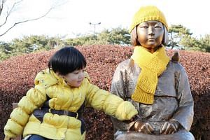 A child sits next to a statue symbolising comfort women in Chuncheon, South Korea, on Dec 9, 2017.