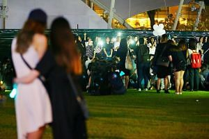 The mood at Hong Lim Park was sombre as many fans hugged and cried. They waved light sticks and smartphones in the air as they sang in unison to the SHINee song Replay.