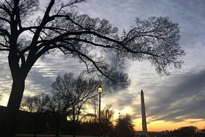 The sun sets behind the Washington Monument in Washington, DC, on Dec 20, 2017, the eve of the winter solstice, the shortest day of the year.