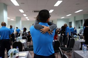 A 38 year-old prisoner hugs his 9 year-old daughter upon seeing her during an open visit at Tanah Merah Prison.