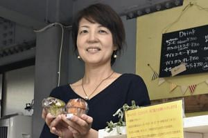 Ms Makoto Nakamura shows okara muffins in her cafe, set up in the renovated garage of her house in Wakaba Ward, Chiba.