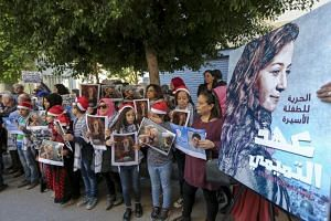 Lebanese and Palestinians from the Khiam Rehabilitation center for the victims of torture (KRC) carry pictures of Palestinian detainees during a protest calling for the freedom of 17-year-old Palestinian girl Ahed Al-Tamimi, in front the Internationa