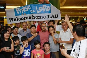 Singaporean cameraman Lau Hon Meng with his friends from the Adam Road Presbyterian Church at Changi Airport on Dec 29.
