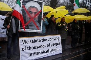 """Opponents of Iranian President Hassan Rouhani protesting outside the Iranian embassy in the British capital London on Sunday. Mr Rouhani (below) has played down the unrest, saying: """"This is nothing."""" He added that """"criticism and protest are an opport"""
