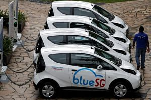 BlueSG electric car-sharing vehicles at a charging station during their launch in Singapore.