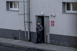 A man smokes outside a dormitory used by North Korean workers at the Partner shipyard in Skolwin, Poland, on Dec 10, 2017.