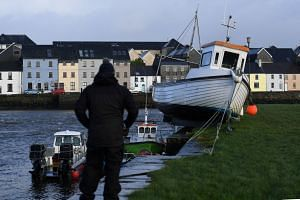 A boat is stranded on the edge of a pier after it was washed there by floods in Galway, Ireland, on Jan 3, 2018.