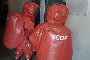 SCDF HazMat specialists (above) during the CNB raid on Dec 6 that led to synthetic cannabis (left) being seized.