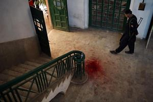 A Pakistani policeman looks a blood-stained floor of an Agriculture Training Institute following an attack by Taliban militants in Peshawar, on Dec 1, 2017.