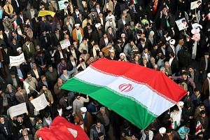 Iranian pro-government supporters march in the city of Mashhad on Jan 4, 2018.