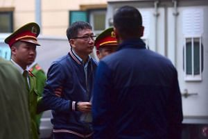 Former oil tycoon Trinh Xuan Thanh, who was reportedly kidnapped from Berlin by Vietnamese security, is lead by policemen to the courtroom at Hanoi People's Courthouse.