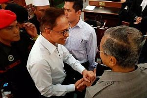 Former Malaysian prime minister Mahathir Mohamad clasping hands with Anwar Ibrahim at the Kuala Lumpur High Court on Sept 5, 2016, at the hearing of an application filed by his jailed ex-deputy.