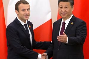 French President Emmanuel Macron shakes hands with Chinese President Xi Jinping during a bilateral meeting on the second day of the G20 leaders summit in Hamburg, Germany on July 8, 2017.