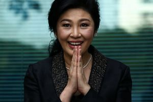 Ousted former Thai prime minister Yingluck Shinawatra greets supporters as she arrives at the Supreme Court in Bangkok on Aug 1, 2017.