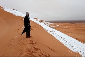 A man looks at at a snow-covered slope in the Sahara in a photo obtained from social media.